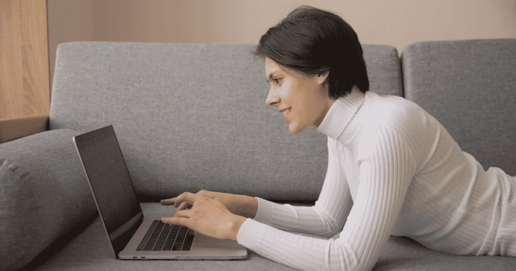 a lady lying on the couch typing on a laptop