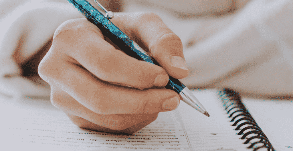 A picture of someone writing on a book with a blue pen: dissertation topics in management